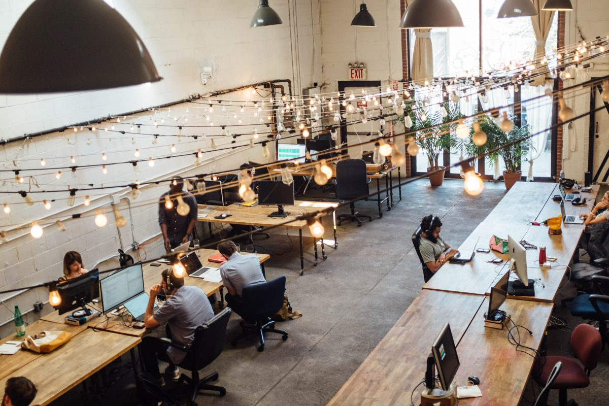 Image of modern workspace with large shared tables and hip old-timey lightbulbs hanging from the ceiling.