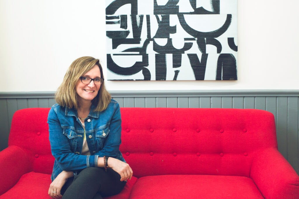 Charlotte Kirby sitting on a couch at the Village Hive